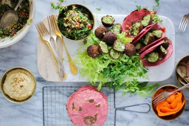 Falafel Tacos on a serving board next to tabbouleh and pink tortillas