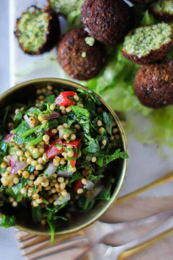 Sorghum Tabboulehin a small bowl next to a platter of falafel