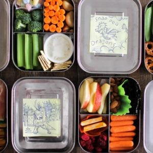 4 colorful bento boxes laid right next to each other with lunchbox drawings