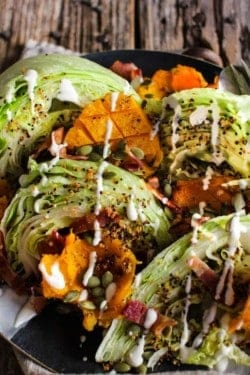iceberg lettuce wedges with roasted butternut squash, crispy quinoa, bacon, and a ranch drizzle