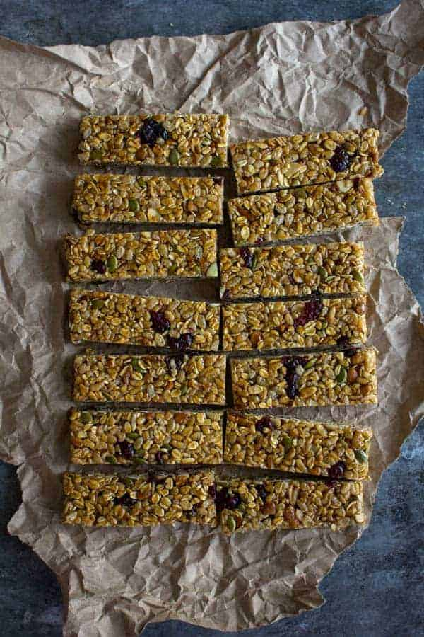 14 rectangular granola bars sit on a piece of crumpled parchment ob a metal table top