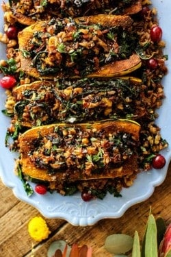 Exotic Rice Stuffed Delicata Squash with Curried Cashew Cream recipe || These curry spiced delicata squash are filled to the brim with an exotic rice blend loaded with onion, garlic, walnuts, kale, and dried bing cherries. This dish is the perfect plant based main dish for your holiday table! || @thismessisours @nutsdotcom