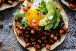 tostada with refried black beans, roasted sweet potatoes, fried egg, and avocado