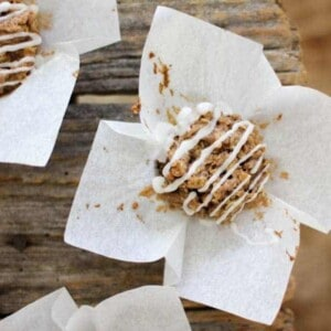 There are 3 iced cinnamon oat cake with white icing drizzle is sitting on top of its white muffin liner that has been peeled back. They are sitting on a wooden table top.