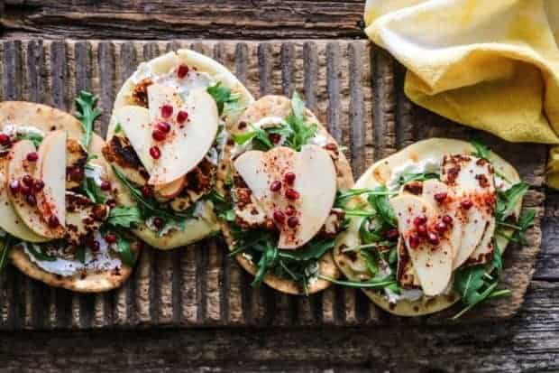 flatbread topped with labneh, arugula, pan seared halloumi, apple, pomegranate, aleppo pepper on a wooden board on a weathered wooden table top with a yellow napkin