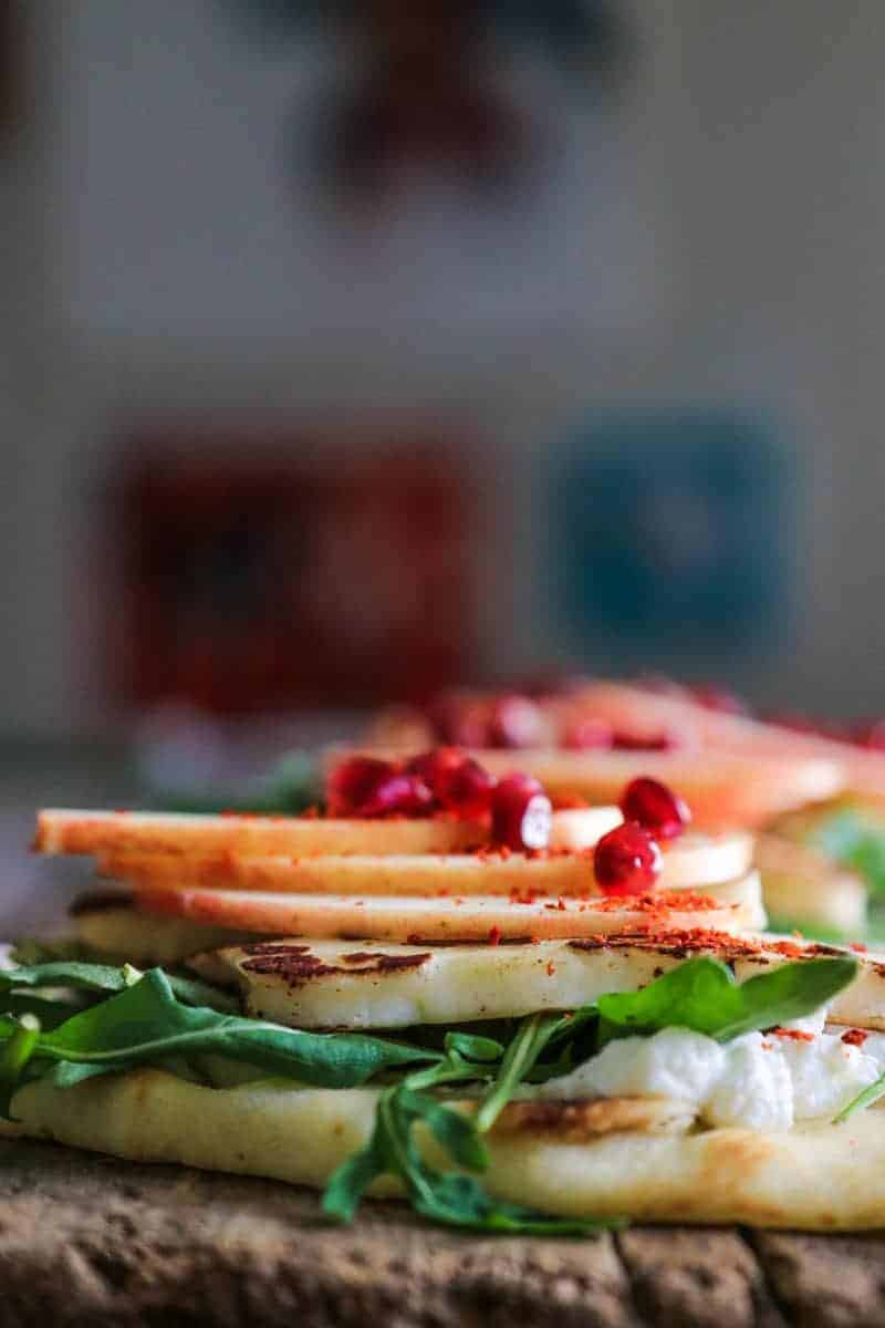 Flatbread layered with labneh, arugula, pan seared halloumi cheese, apple slices, aleppo pepper, and pomegranate