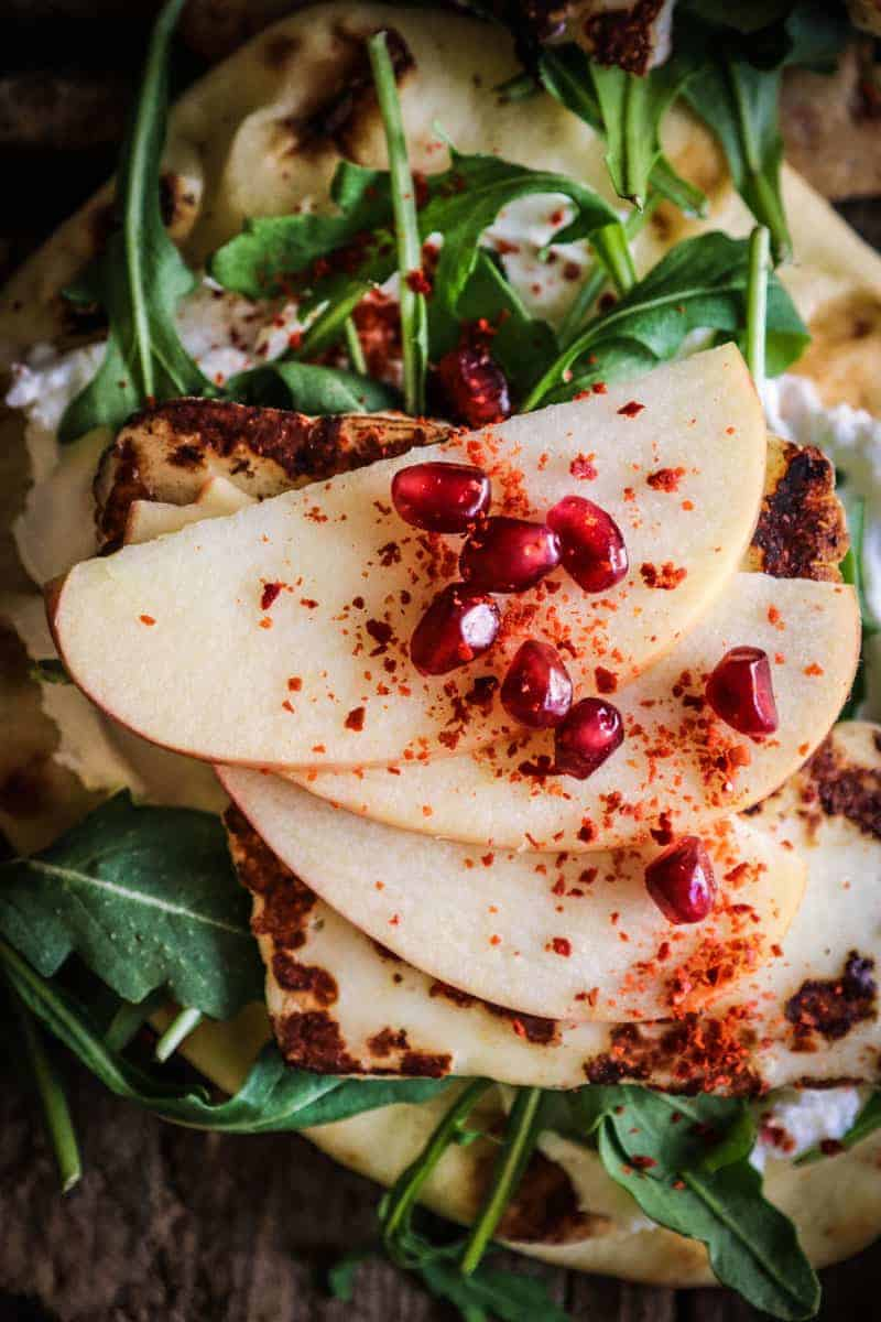 naan layered with labneh, arugula, halloumi cheese, thinly sliced apples, pomegranate, and aleppo pepper