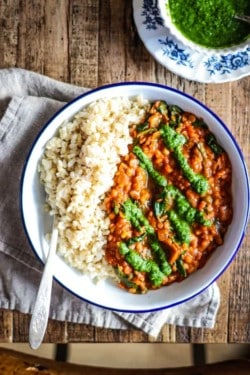bowl of brown rice with red lentil coconut curry and drizzled with green cilantro chutney