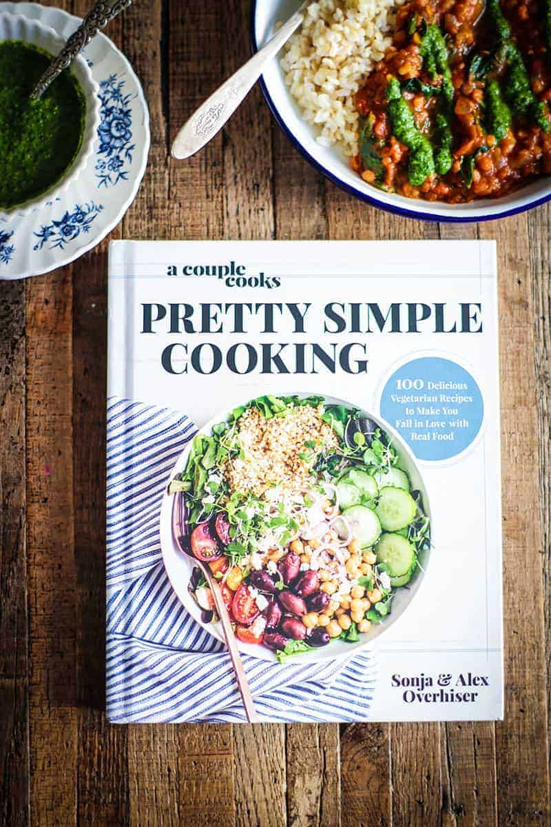 A bowl of curry and a bowl of chutney with a copy of teh cookbook Pretty Simple Cooking