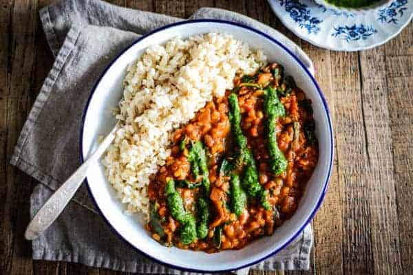 bowl of brown rice with red lentil coconut curry and cilantro chutney drizzled on top