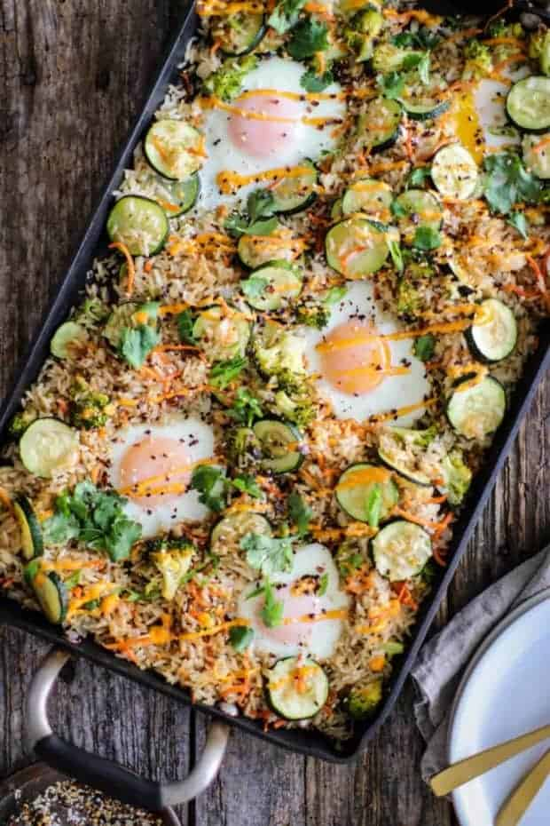 fried rice with zucchini, broccoli, carrots, and eggs on a sheet oan with a drizzle of sriracha mayo