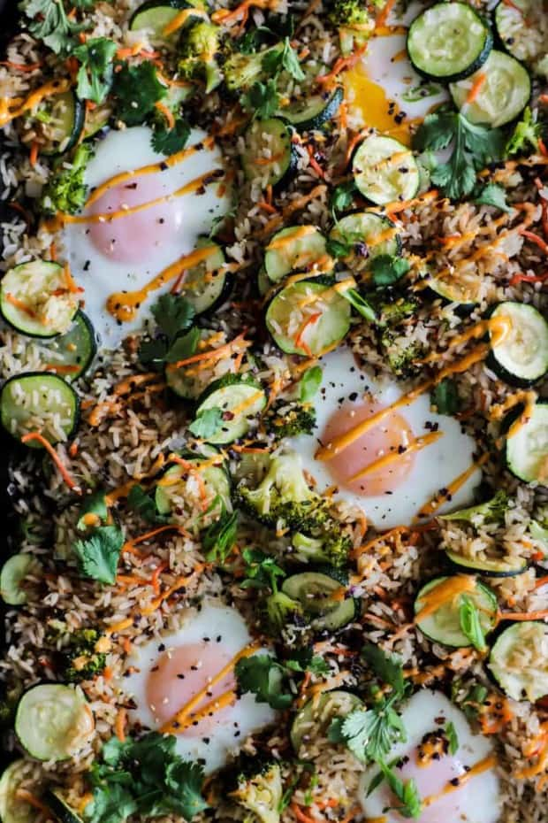 sheet pan full of oven fried rice, zucchini sliced, carrot, broccoli, and herbs with eggs and a sriracha mayo drizzle.