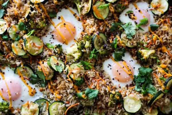 fried rice on a sheet pan with carrots, zucchini, sunny side up eggs and herbs
