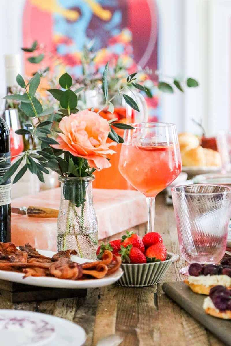 brunch table with flowers, sangria, strawberries, and bacon