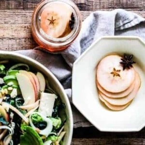 Salad in an off white stone ware bowl made of greens, fresh sliced apples, shaved fennel, chopped pickled apples, and white cheddar cheese chunks on a tobacco lathe table top with an octagonal shaped off white bowl filled with slices of pickled apples and a star anise on top of a linen napkin. There is also a mason jar filled with slices of pickled apples.
