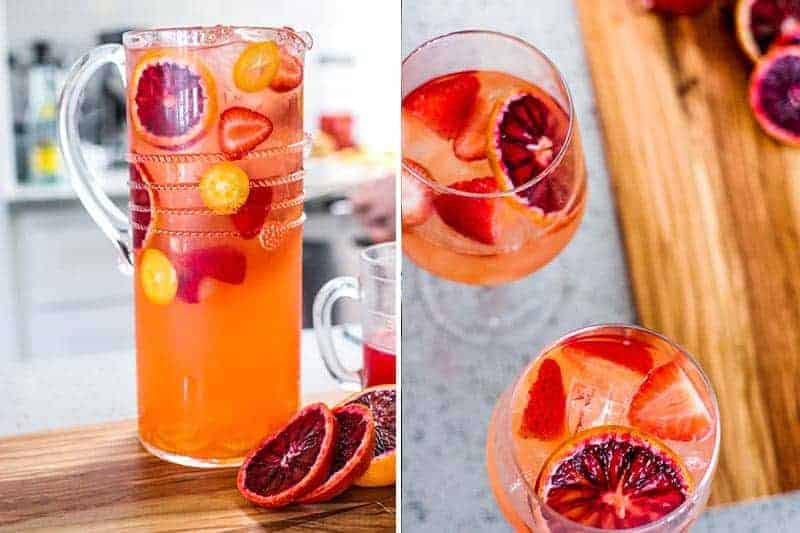 Pitcher and glasses of Blood Orange Ginger Sangria with fresh oranges, strawberries, raspberries and kumquats