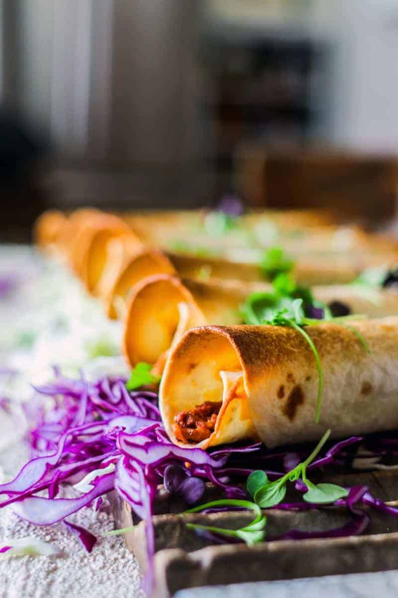 Vegetarian Chili Cheeseburger Taquitos on top of purple cabbage