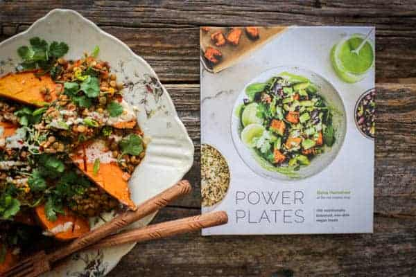 Roasted sweet potato smothered in Moroccan spiced lentils then drizzled with tahini dressing and a copy of the cookbook Power Plates