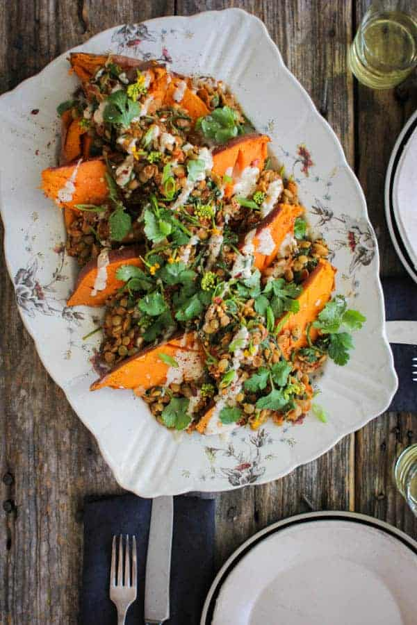 A large rectangular platter is lined with roasted sweet potatoes halves which are topped with spiced lentils, lemon tahini dressing, and fresh cilantro. Teh platter sits on a weathered wooden table along with 2 place settings.