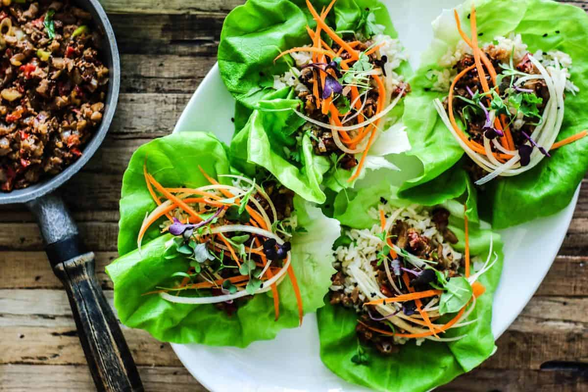 lettuce cups with brown rice, hoisin mushroom filling, shredded carrots, micro greens, and sesame seeds.