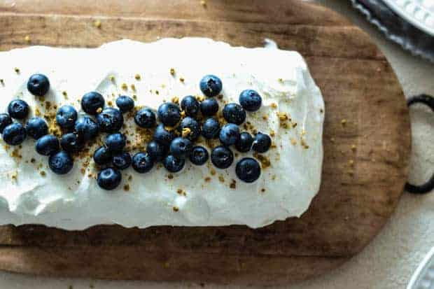 looking down onto a rectangular cake that is frosted with white whipped cream icing and sprinkled with fresh blueberries and yellow bee pollen. Cake is on a wooden board with a metal handle on a light colored table.