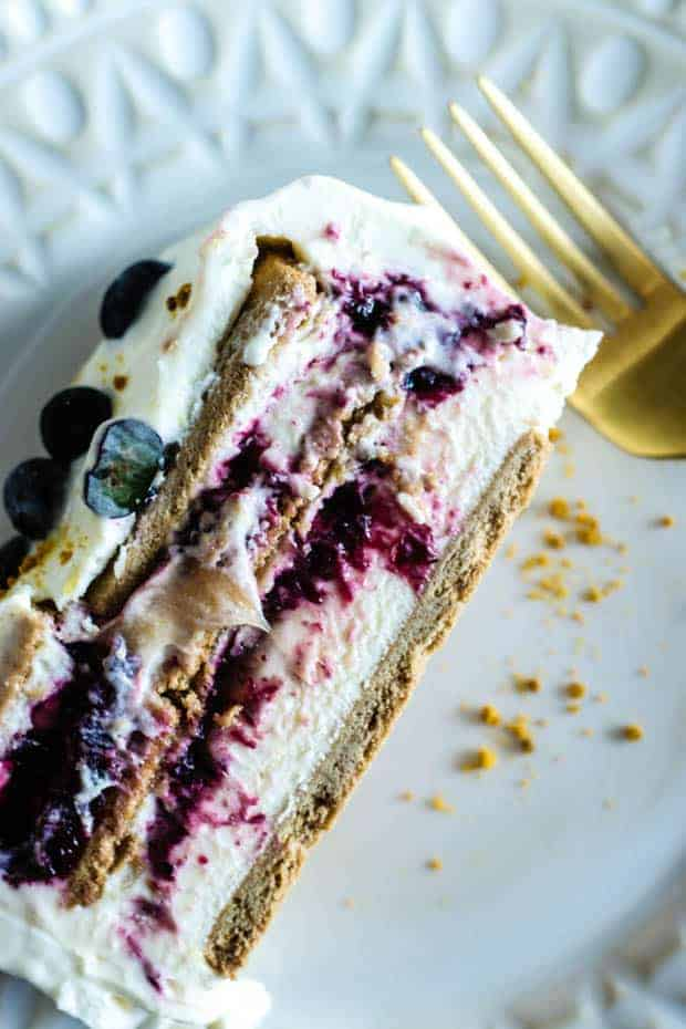A slice of blueberry lavender icebox cake. Layers of graham crackers, whipped marscapone cream, and blueberry lavender jam. Cake is iced with whipped mascarpone cream and a sprinkle of fresh blueberries. Cake slice is plated on an off-white plate with a decorative edge and a gold fork.