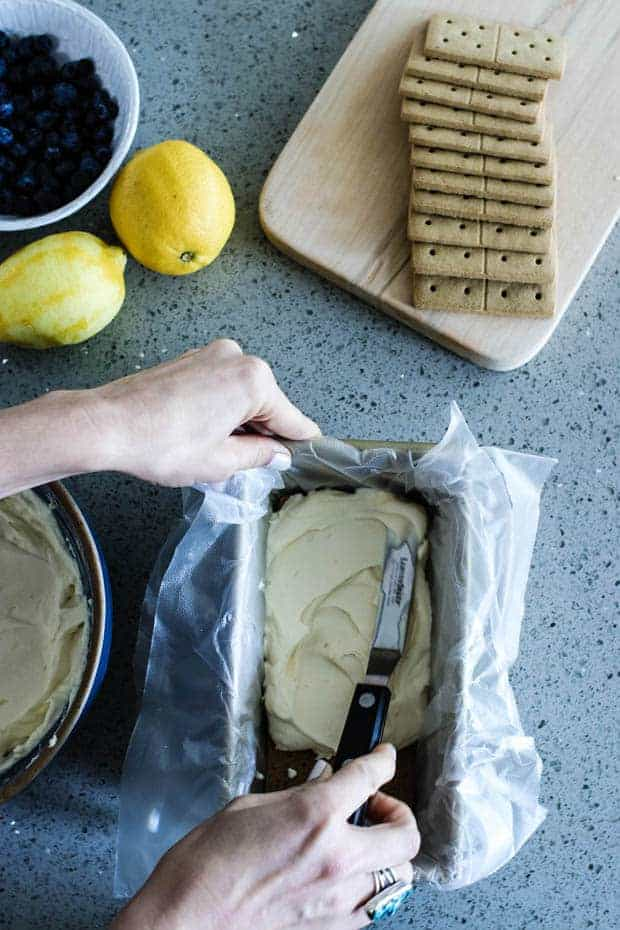 A woman spreading whipped cream onto a layer of graham crackers that are in a loaf pan that is lined with plastic wrap hanging over the sides. She is working on a gray quartz countertop that also has a wood board with graham crackers, awhite bowl of blueberries, 2 lemons, one has been zested and one has not.