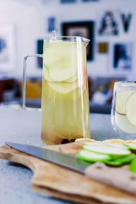 Pitcher of white sangria with apple slices on the counter and a cutting board with apples and a knife in the foreground. Artwork hanging walls in the background.