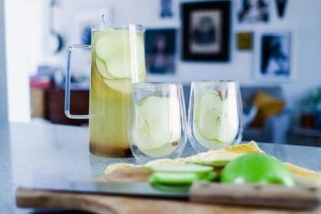 Pitcher and 2 glasses of white sangria with apple slices on the counter and a cutting board with apples. Pictures hanging on the wall in the background.