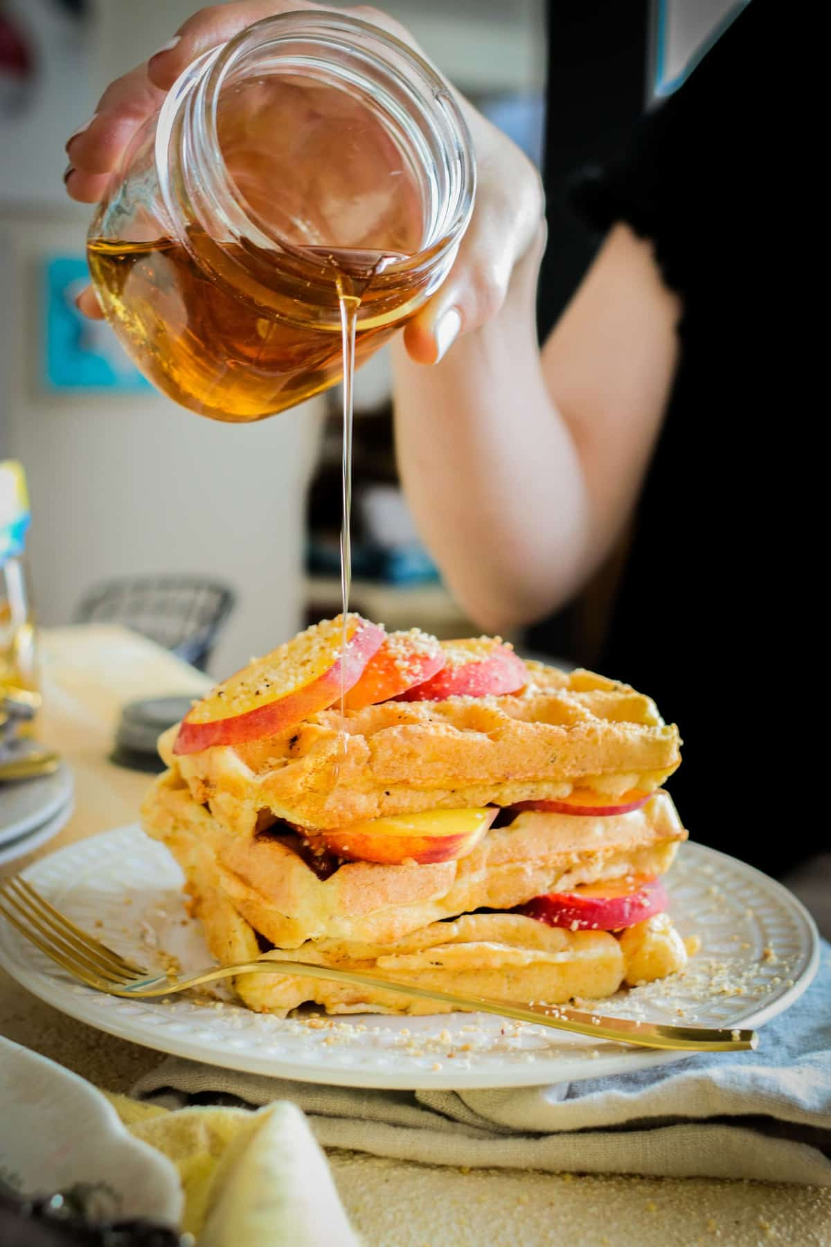 Stack of waffles with sliced peaches being drizzled with maple syrup