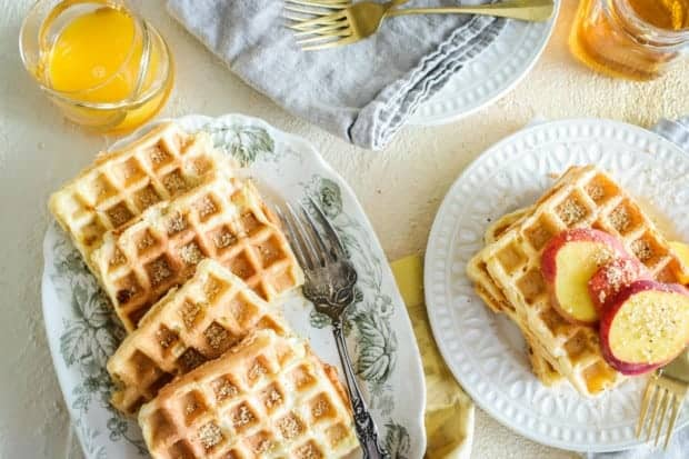 waffles on serving plate and in a stack with sliced peaches on top. Maple syrup and orange juice on the side.