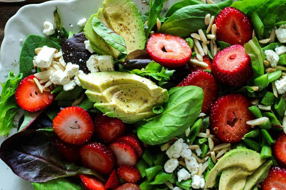Salad of baby greens, sliced strawberries, avocado, snap peas, toasted almonds, and feta with a strawberry poppyseed dressing.