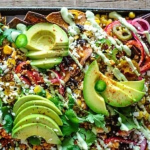 Sheet pan covered in sweet potato tortilla chips and blue corn tortilla chips then topped with fire roasted corn kernels, black beans, jalapeños, pickled red onions, thinly sliced avocado, Aleppo pepper flakes and a green roasted poblano cashew cream drizzle.
