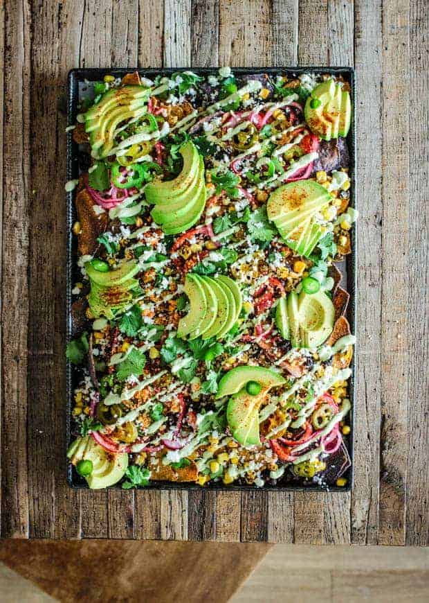 A sheet pan of nachos covered in a variety of toppings like corn, black beans, pickled onions, and avocado slices on top of a wood table top . You can also see a wooden chair in the images as well.