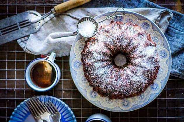 Apple chai monkey bread on a blue and white plate, dusted with powdered sugar. White mugs with a blue rim of chai tea on the side
