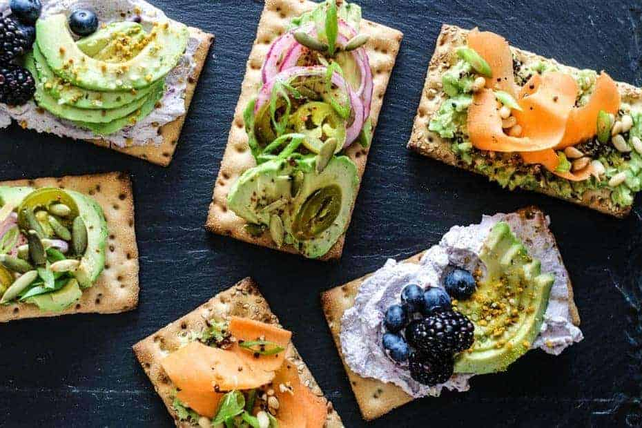 3 types of gluten free crispbreads: savory with avocado, carrot, crispy quinoa, pepitas, sweet with jam flavored whipped cream, avocado slices, mixed berries, bee pollen, and hemp hearts, and spicy with sliced avocado, citrus pickled onions, pickled and fresh jalapeño slices, pepitas, and green onions. All arranged on a black slate tray.