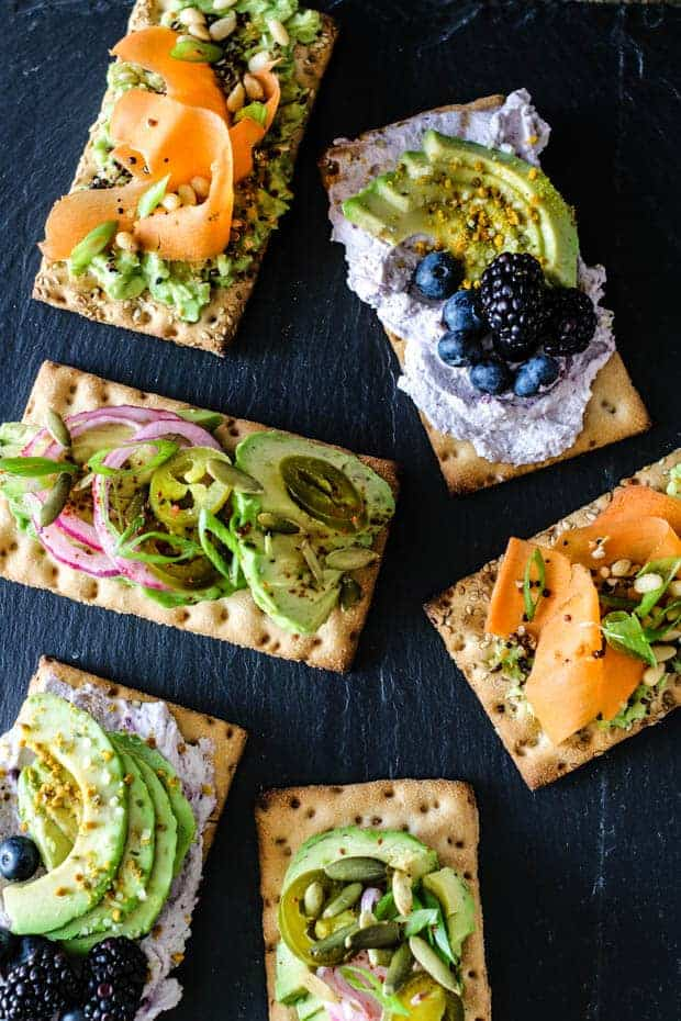 6 various avocado crispbreads with toppings arranged on top of a black slate board