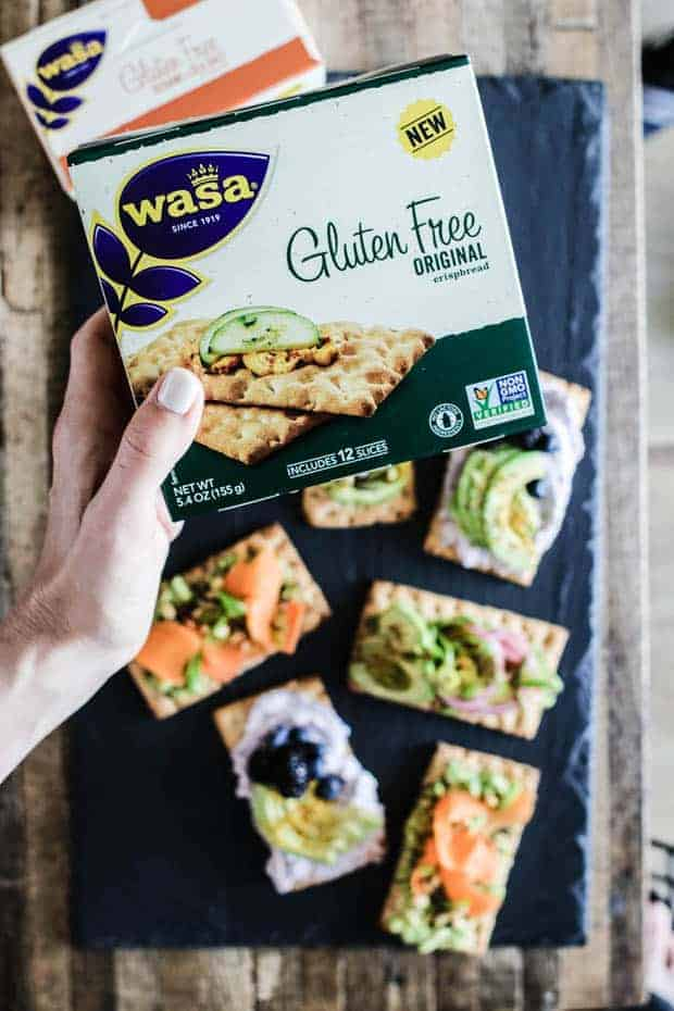 a variety of avocado crispbreads arranged on a slate board on top of a wood lathe table top. a hand holding a box of @wasa gluten free crispbreads