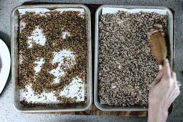 2 baking pans side by side on gray kitchen counter ; one with leftover, cooked tricolor quinoa and one with quinoa after it has baked to a crisp golden brown.