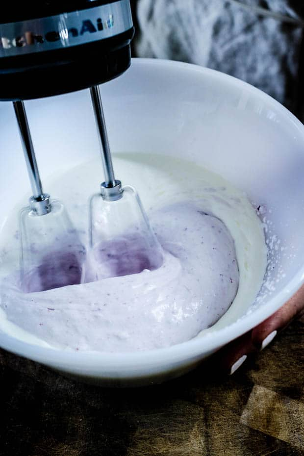 A white mixing bowl with a hand held mixer beating heavy cream. Teh whipped cream has turned half white/half purple from the addition of blueberry jam in the whipped cream