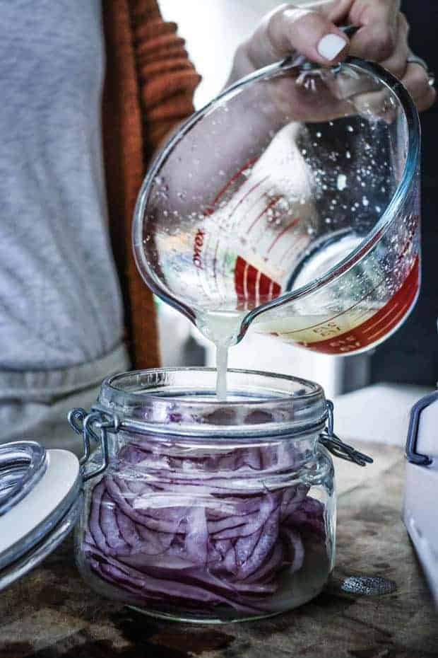 woman in white shirt and orange sweater pouring lime juice from a measuring glass into a jar of thinly sliced red onions that is setting on top of a wooden cutting board.