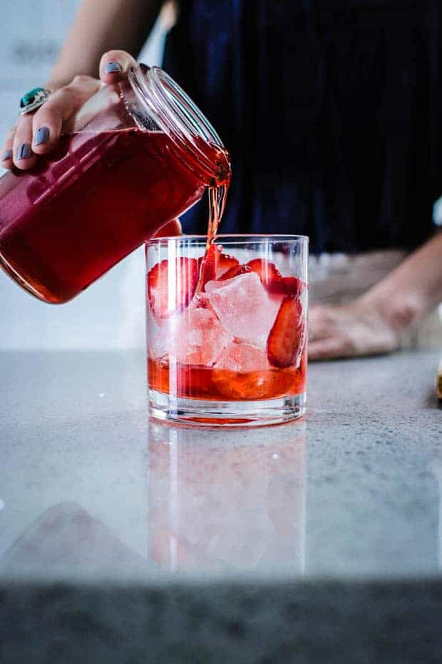 A woman pouring a red liquid from a glass jar into a glass with ice cubes and slices of strawberries
