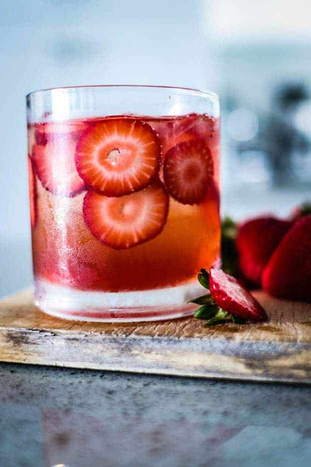 A red drink in a clear glass with ice cubes and slices of strawberries floating in it. Teh glass is on top of a wooden board that is placed on a grey kitchen counter and there are sliced berries next to the drink