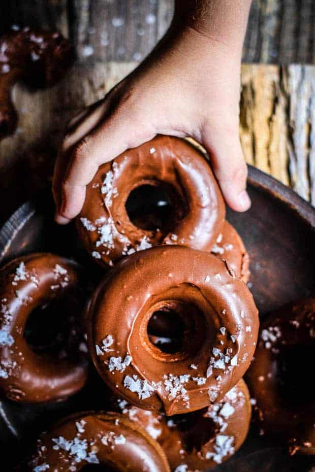 A dark brown wooden bowl filled with chocolate peanut butter donuts iced with chocolate icing and sprinkled with flaky sea salt. There is a little boys hand reaching in and grabbing a donut. Teh bowl is placed on a gray wooden table.