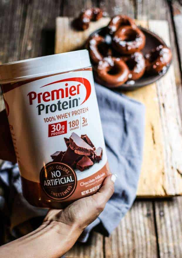 A woman's hands holding a container of Premier Chocolate Protein Powder. In the background there is a wooden table top with a dark brown bowl filled with chocolate donuts iced with chocolate icing and sprinkled with flaky sea salt. There is also a gray linen napkin on the table top.