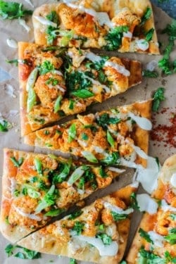 Triangles of Roasted Buffalo Cauliflower Flatbread on top of crinkled brown parchment paper. The flatbread is topped with orange buffalo flavored cauliflower, a drizzle of ranch dressing, green onion slices, and minced cilantro.