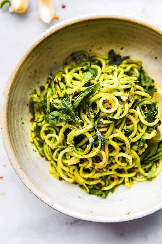 "An off white bowl of zucchini ""noodles"" tossed in a green pesto. and a few basil leaves. The bowl sit son a white surface with a few garlic cloves on top."
