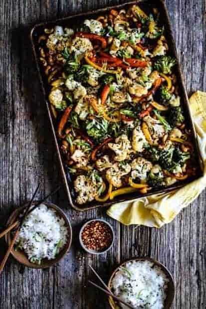 A large sheet pan filled with roasted vegetables like cauliflower, broccoli, red and yellow green peppers, and cashews sits on top of a yellow dish cloth on top of a wooden table. There are also 2 small brown bowls filled with white rice an da small bowl of red chili pepper flakes.