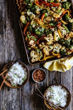 A large sheet pan is sitting on top of a wooden table. The sheet pan is full of roasted white cauliflower, red and yellow bell peppers, and green broccoli. The sheet pan is sitting on top of a yellow and white kitchen towel. Also on the table there are 2 small brown bowls filled with rice and garnished with green onions, basil blossoms, and chive blossoms. Each bowl has a set pf wooden chopsticks on top. There is also a small dish on the table that is full of red pepper flakes.