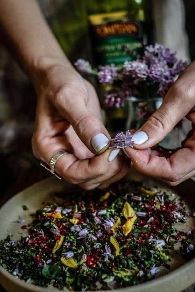 There is a cream colored plate filled with green chopped herbs and edible flower petals. A woman's hands with white manicured nails and a large silver ring on her right pointer finger is plucking the petals from a purple chive blossom over the platter. There is a bottle of olive oil in the background.